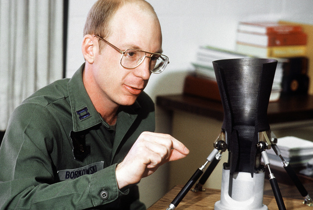 CAPT. Mark Borkowski, chief of the Aerospace Launched Missile Branch of the Air Force Astronautics Laboratory, explains a cutaway scale model of a rocket motor nozzle