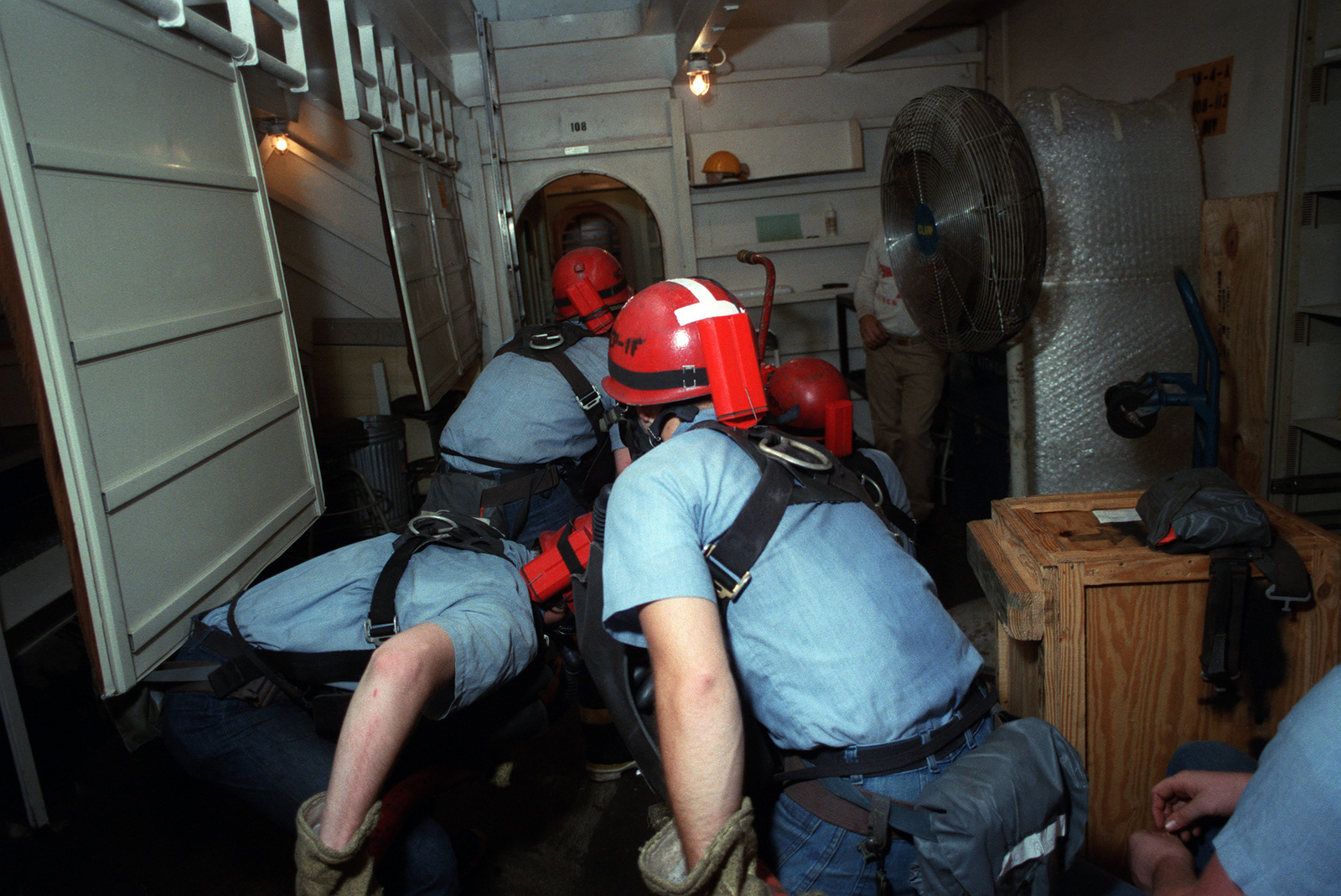 Damage control personnel wearing oxygen breathing apparatuses advance through a compartment during a firefighting drill on board the US Navy (USN) Nuclear-powered Aircraft Carrier USS DWIGHT D. EISENHOWER (CVN 69)