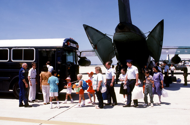 Lieutenant Colonel George Shy of the 31st Aeromedical Evacuation Squadron says goodbye to families boarding a bus which has driven up to the C-141B Starlifter aircraft on the flight line. The families have been guests of Jason's House, a program that provides free, week-long vacations in Myrtle Beach, South Carolina for families of seriously ill children