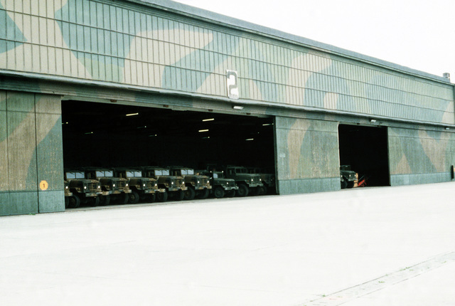 M-923 5-ton cargo trucks and other U.S. Marine Corps equipment are parked in a holding facility