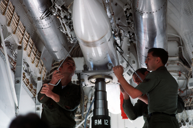 Members of the 28th Munitions Maintenance Squadron bolt a BDU-38 practice bomb to the weapons release system in a B-1B aircraft during Phase II of exercise Proud Shield '88, in which KC-135 Stratotanker aircraft and B-1B crews hold navigation, bombing and refueling competitions