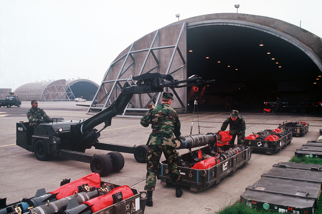 Munitions crew members use an MJ1 weapons loader to remove Durandal bombs from their crates. The French-developed Durandal, which optimizes its angle of attack after release to prevent ricochets and then accelerates rapidly, is intended for prolonged disabling of enemy runways and other targets in which the effects of deep bomb penetration will maximize damage