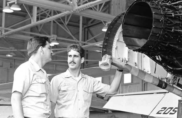 Naval officers inspect the tailhook of an F/A-18A Hornet aircraft