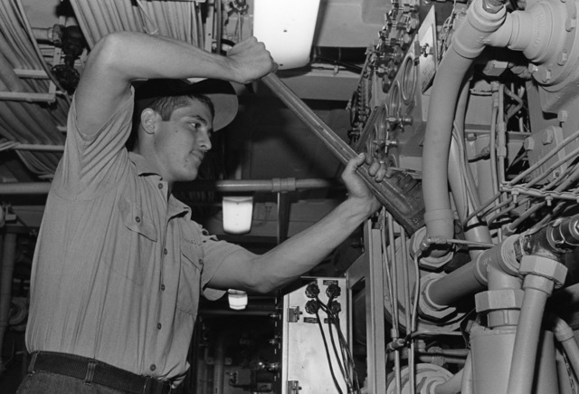 PETTY Officer Third Class (PO3) Kevin L. Hackett tightens a fitting on a high pressure air compressor aboard the destroyer USS INGERSOLL (DD 990)