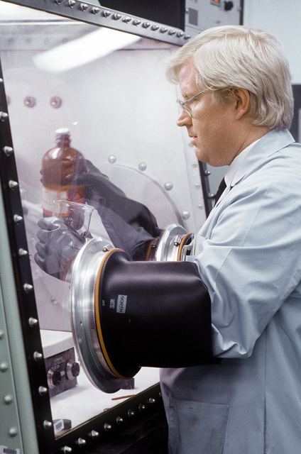 Robert Chapman, a civilian research chemist with the Aerospace Launched Missile Branch of the Air Force Astronautics Laboratory, mixes a solution from behind a sealed environmental barrier