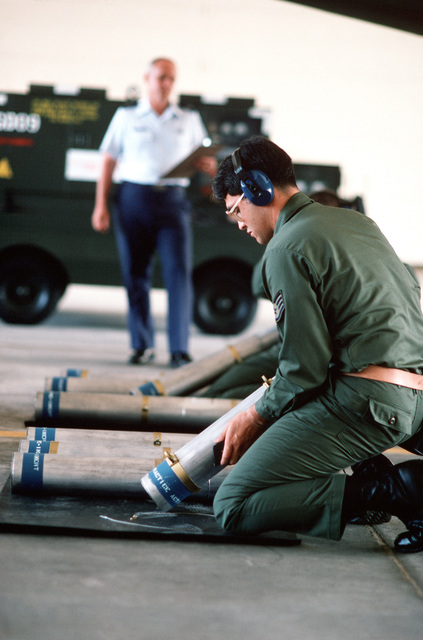 STAFF Sergeant (SSGT) Kevin McGuire prepares an inert flare during an OV-10 Bronco aircraft static load as CHIEF MASTER Sergeant (CMSGT) Dave Ferry, judge, stands by during Sabre Spirit, Pacific Air Forces'first command-wide competition to test the skill