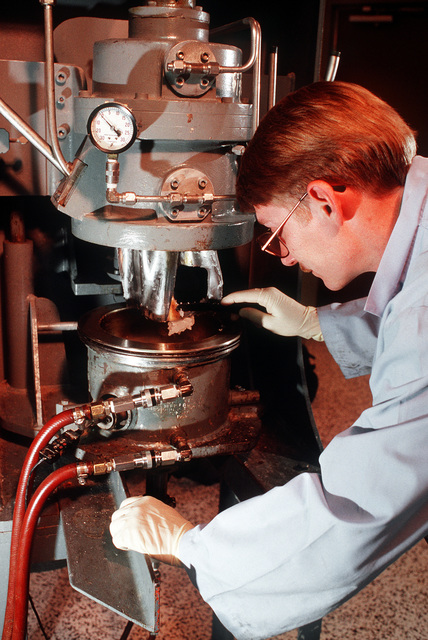 STAFF SGT. Scott F. Strader, a research and development mechanic at the Air Force Astronautics Laboratory, collects a sample of solid rocket motor proellant from a mixing blade