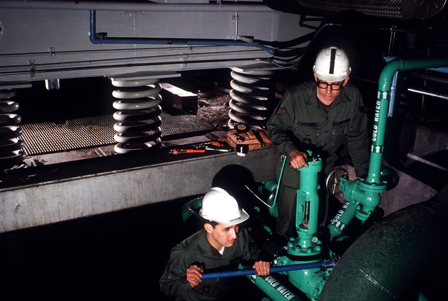 Two airmen work on the water-handling system for the North American Aerospace Defense Command (NORAD) Cheyenne Mountain Complex