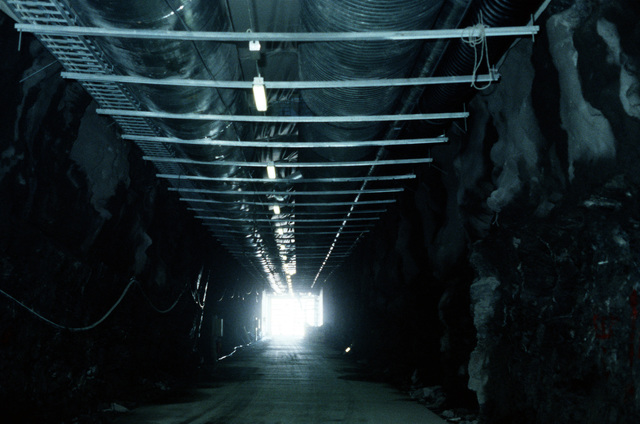 Ventilation pipes and support structures line a tunnel leading to a pre-positioning cave which is used to store U.S. Marine Corps equipment