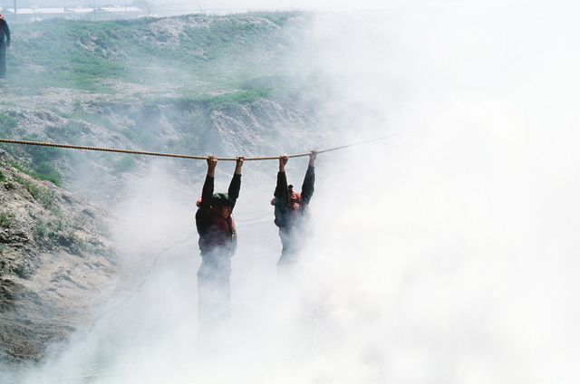 U. S. Navy Basic Underwater Demolition/Sea-Air-Land (BUD/S) trainees negotiate an obstacle as part of their training