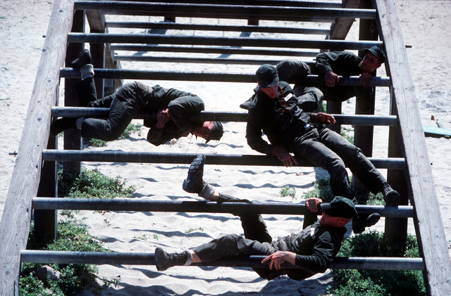 U. S. Navy Basic Underwater Demolition/Sea-Air-Land (BUD/S) trainees participate negotiate an obstacle as part of their training