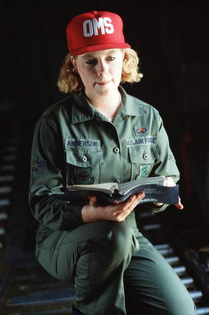 AIRMAN First Class (A1C) Debra Jane Anderson, C-141B Starlifter aircraft loadmaster, reads a US Air Force technician manual while sitting on a loading ramp in an aircraft