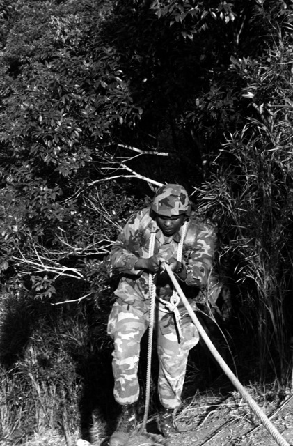 LCPL Michael Walker begins a hasty rappel down a steep slope during field training at the Northern Training Area