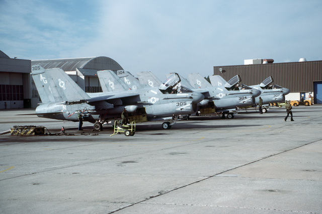 A right side view of three Attack Squadron 46 (VA-46) A-7E Corsair II aircraft parked on the flight line