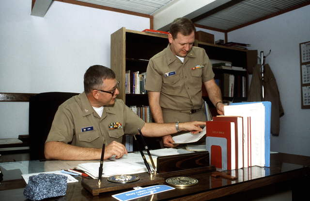 Captain Howe, seated, and Lieutenant J.G. Snowdon, both chaplains serving aboard the air station, draw up plans for a fund-raising event