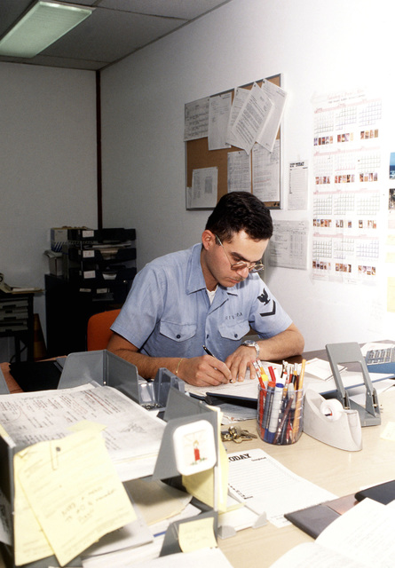 Religious Program SPECIALIST 3rd Class Rivera tends to his paperwork. Rivera is one of four religious program specialists serving at the air station
