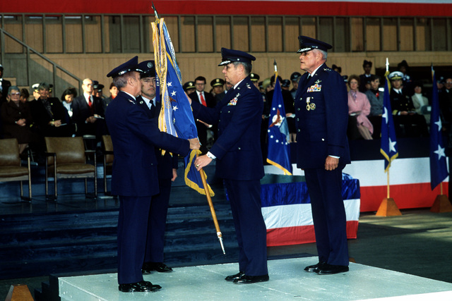 LGEN Edward L. Tixier, U.S. Air Forces, Japan, and 5th Air Force commander, stands by at right as GEN Jack Gregory, commander in chief of Pacific Air Forces, presents the unit colors to LGEN James B. Davis during the ceremony at which Tixier relinquishes his command to Davis