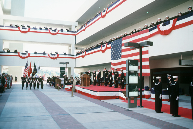 A color guard passes the reviewing stand during the opening of the new Naval Hospital, San Diego.  On the stand are, from left to right:  Captain (CAPT) C.A. Wesolowski, hospital commander; Rear Admiral (RADM) (upper half) H.J.T. Sears, commander, Naval Medical Command, Southwest Region; Vice Admiral (VADM) J.A. Zimble, surgeon general, US Navy; Rear Admiral (RADM) (upper half) B.F. Montoya, commander, Naval Facilities Engineering Command; and Chaplain Captain (CAPT) Kenneth F. Kieffer