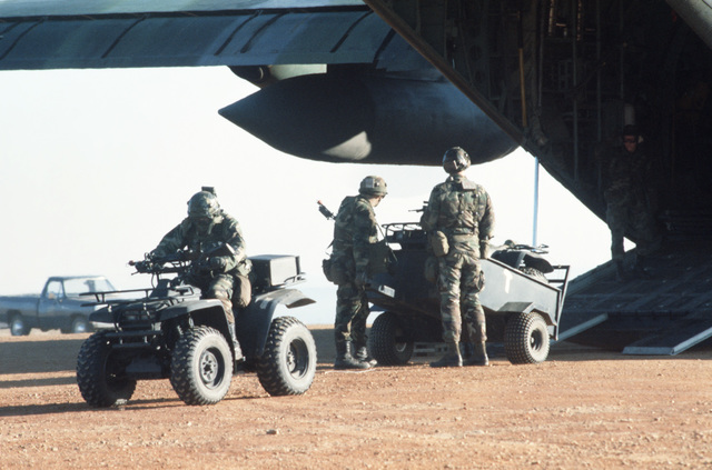 A combat light auxiliary weapon (CLAW) waits for a trailer to be connected at the rear of a 16th Tactical Airlift Training Squadron C-130 Hercules aircraft during an air base ground defense training exercise