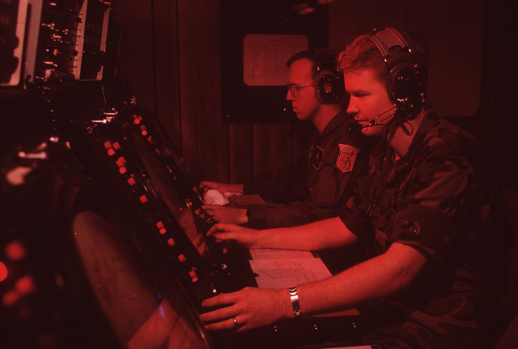 2LT James Romani, foreground, and CPT Steve Cichocki monitor the positions of aircraft operating on the Air Combat Maneuvering Instrumentation (ACMI) range. Romani is the ACMI range weapons director; Cichocki is the director of radar operations