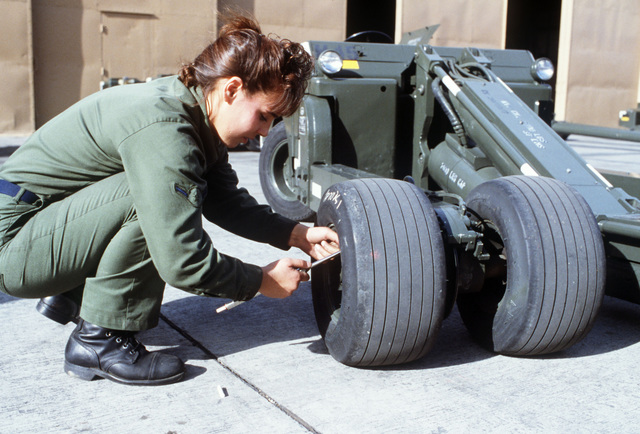 A member of the 37th Equipment Maintenance Squadron checks the tire pressure on a SATS weapons loader in the aircraft ground equipment yard