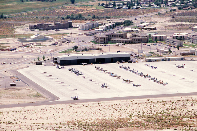 An aerial view of jets on the flight line, hangars, and buildings, during Exercise Gallant Eagle '88