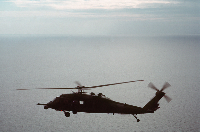 An air-to-air left side view of an MH-60G Pave Hawk helicopter over the water near Eglin Air Force Base.  The helicopter is undergoing testing for use by the 55th Special Operations Squadron