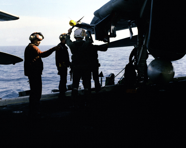 Ordnancemen check the mounting of an AIM-9L Sidewinder missile on the wing of an F-14A Tomcat aircraft aboard the nuclear-powered aircraft carrier USS DWIGHT D. EISENHOWER (CVN 69)