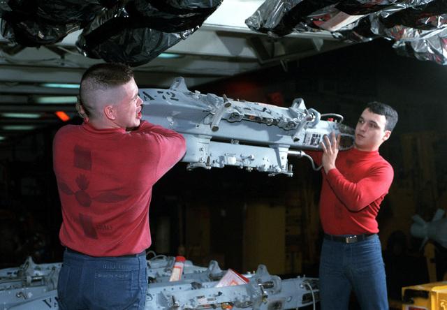 Ordnancemen on the nuclear-powered aircraft carrier USS DWIGHT D. EISENHOWER (CVN 69) carry an ordnance triple ejector rack (TER)