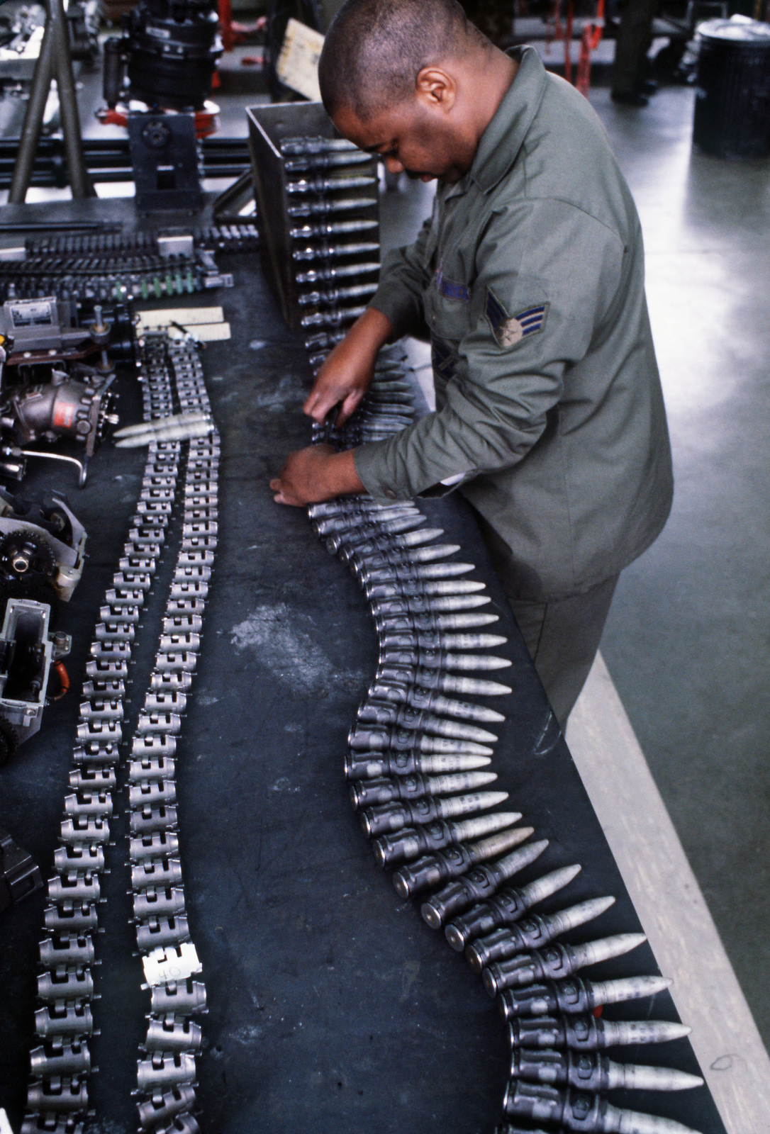 SRA Mark Walker of the 37th Equipment Maintenance Squadron works on a belt of 20mm cannon ammunition in the squadron armament shop