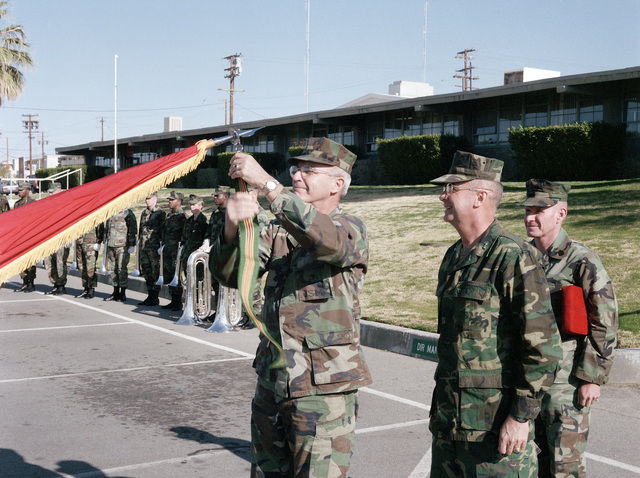 Major General (MGEN) J.J. McMonagle, commanding general, 1ST Marine Expeditionary Force, attaches the Meritorious Unit Commendation streamer to the colors of the 7th Marine Expeditionary Brigade as MGEN Gene A. Deegan, commanding general of the Marine Corps Air-Ground Combat Center, and Sergeant Major (SGM) Doug Wildenhaus, look on