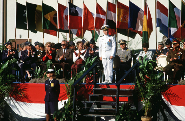 Commodore (CMDR) Cooper, foreign service officer, stands on the reviewing stage during the opening ceremony of the 1988 Conseil International Du Sport Militaire's Cross Country Championship (CISM)