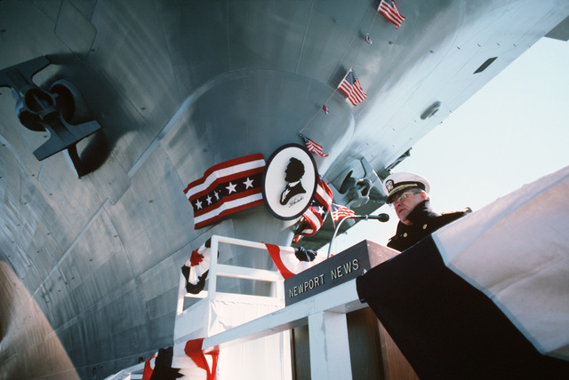 Admiral (ADM) Carlisle A.H. Trost, chief of naval operations, delivers a speech at the christening ceremony of the nuclear-powered aircraft carrier USS ABRAHAM LINCOLN (CVN 72) as the LINCOLN's bow, decorated with a silhouette of its namesake, looms over the speakers platform.  The ceremony is taking place at Newport News Shipbuilding and Dry Dock Co
