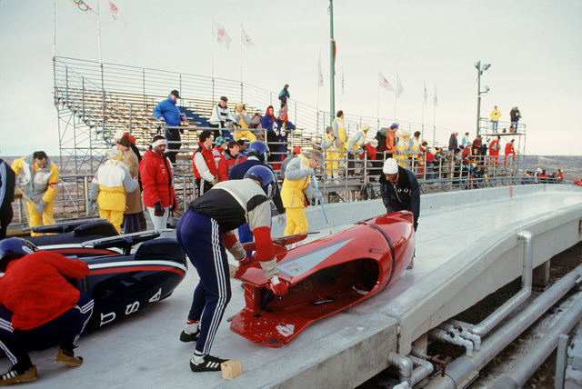 Captain (CPT) William White, 3245th Security Police Squadron, US Air Force, forefront, and another member of the US Bobsled Team position a bobsled at the starting line during the bobsledding competition during the 1988 Winter Olympics