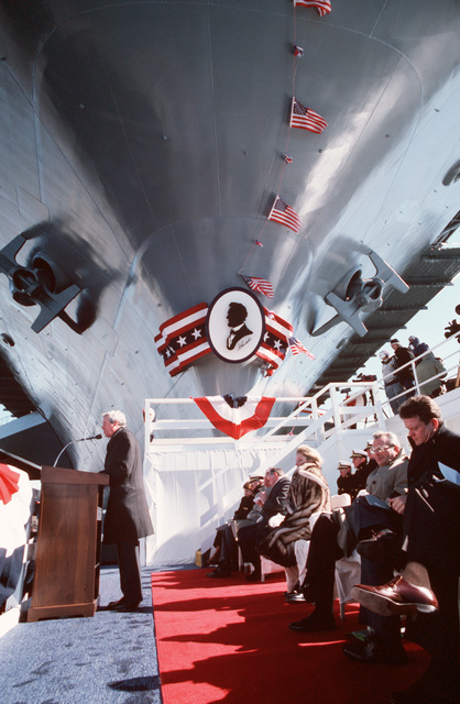 Edward J. Campbell, president of Newport News Shipbuilding and Dry Dock Co., delivers a speech at the christening ceremony of the nuclear-powered aircraft carrier USS ABRAHAM LINCOLN (CVN 72) as the LINCOLN's bow, decorated with a silhouette of its namesake, looms over the speakers platform.  Joann Webb (seated, behind Campbell, ship's sponsor and wife of Secretary of the Navy James H. Webb Jr., will perform the christening