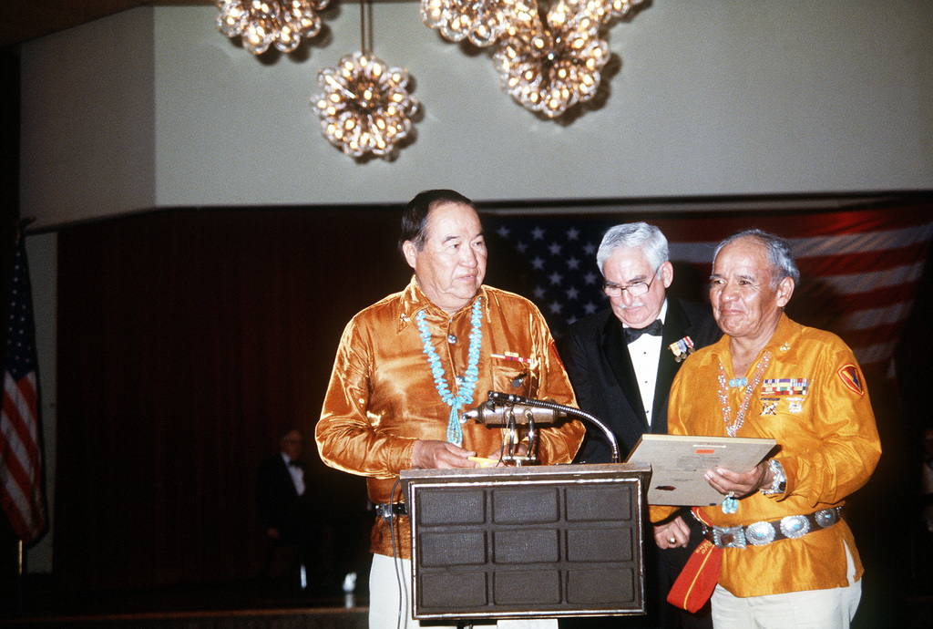 President of the Navajo Code Talkers, left, Joe Garza, ceremony chairman, center, and the vice-president of the Code Talkers present the commandant of the Marine Corps GEN. Alfred M. Gray Jr. with a copy of the Navajo Code Talkers Marine Corps hymn
