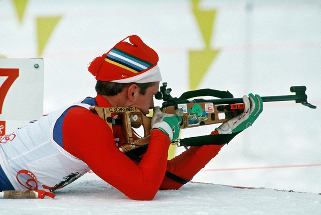 SPECIALIST Fourth Class (SPC) Curtis Schreiner, New York Army National Guard, sights a target from prone position during the biathlon competition, part of the 1988 Winter Olympics