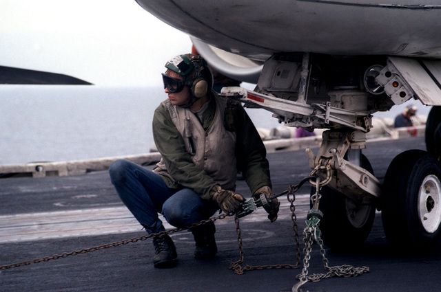 A flight deck crewman tightens the tie-down chains attached to the nose gear of an aircraft aboard the nuclear-powered aircraft carrier USS DWIGHT D. EISENHOWER (CVN 69)