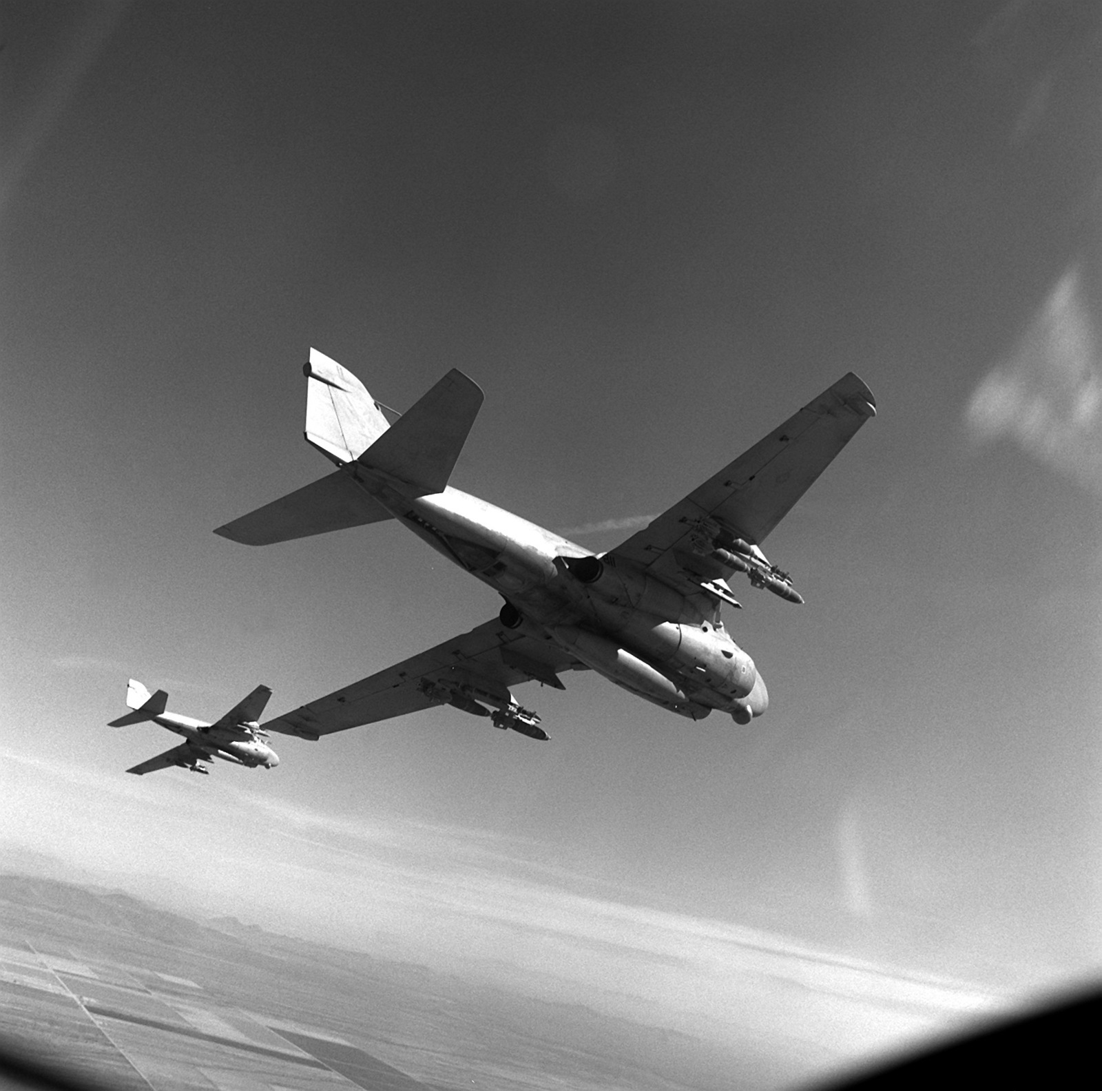 An air-to-air right underside view of two Attack Squadron 128 (VA-128) A6E Intruder aircraft carrying Mark-82 500-pound bombs. The aircraft are en route Naval Air Facility, El Centro, Calif