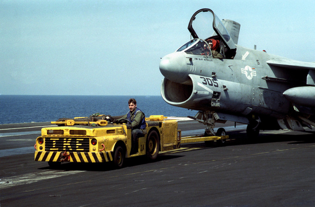An MD-3A tow tractor pulls an Attack Squadron 46 (VA-46) A-7E Corsair II aircraft across the flight deck of the nuclear-powered aircraft carrier USS DWIGHT D. EISENHOWER (CVN 69)