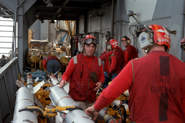 Aviation ordnancemen aboard the nuclear-powered aircraft carrier USS DWIGHT D. EISENHOWER (CVN-69) discuss the movement of AIM-7 Sparrow missiles, foreground, and other ordnance onto the flight deck for the arming of aircraft