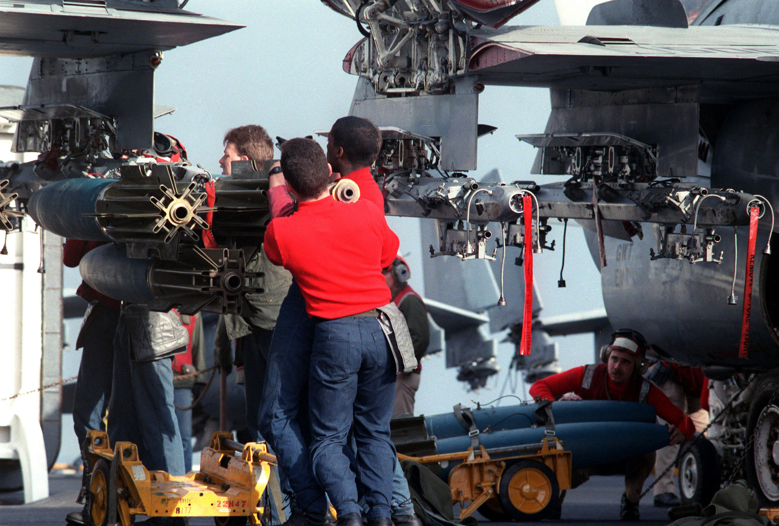Aviation ordnancemen hoist a Mark 82 500-pound high-drag