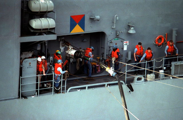 Crewmen at an underway replenishment station aboard the destroyer USS STUMP (DD 978) stand by as fuel is passed to their ship from the nuclear-powered aircraft carrier USS DWIGHT D. EISENHOWER (CVN 69)