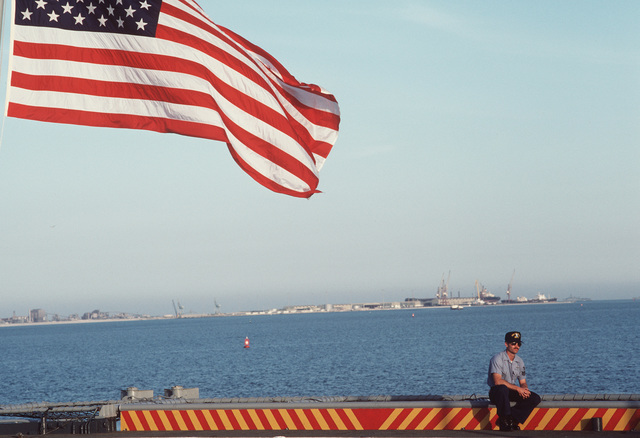 A member of the Middle East Force staff sits on the edge of the deck of the command ship USS CORONADO (AGF 11).  The CORONADO is docked in port at Bahrain