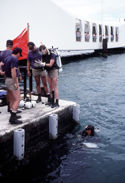 A Navy diver from Mobile Diving Salvage Unit One prepares for a survey dive as tourists watch from the USS ARIZONA (BB-39) Memorial. Members of MDSU One are studying the wreck of the battleship USS ARIZONA (BB-39) as part of Project Sea Mark, a four-year undersea survey and mapping study of naval historic sites. The study is being conducted in conjuction with the U.S. Park Service's Submerged Cultural Resource Unit