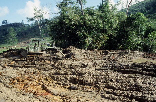 A crawler/loader clears ground for a road being built by West Virginia Army National Guard personnel during Task Force III, a civic action program in which the guard is also providing health and veterinary services for residents of the Puenta Grande area