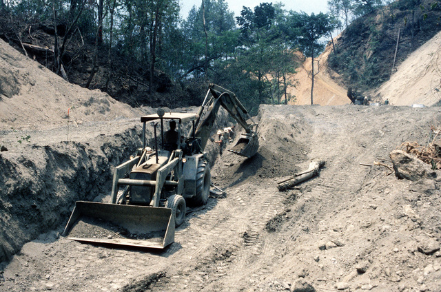 A loader/excavator operated by a member of the West Virginia Army National Guard works on a roadbuilding project during Task Force III, a civic action program in which the guard is also providing health and veterinary services for residents of the Puente Grande area