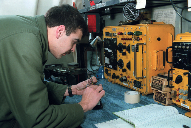 A Sailor tinkers with a circuit board in the calibration shop on board the US Navy (USN) Nuclear-powered Aircraft Carrier USS DWIGHT D. EISENHOWER (CVN 69)