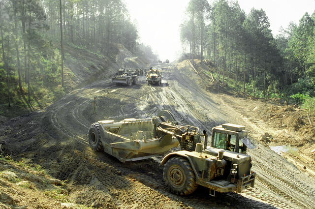 A West Virginia Army National Guard earthmoving scraper works on a roadcut during Task Force III, a civic action program in which the guard is also providing health and veterinary services for residents of the Puenta Grande area