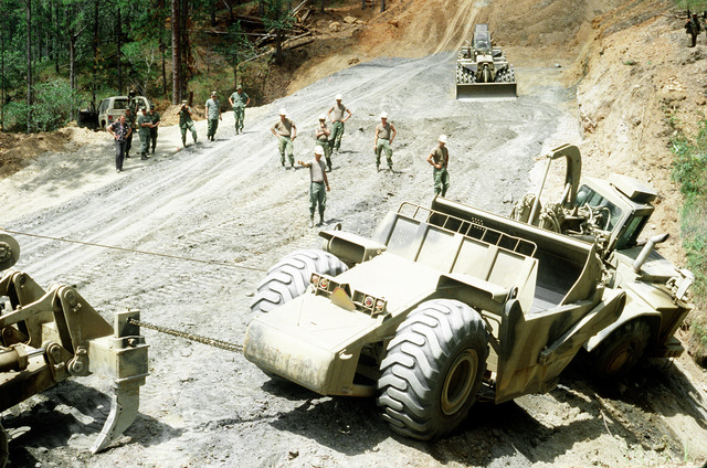 A West Virginia Army National Guard soldier directs an earthmoving scraper engaged in road construction during Task Force III, a civic action program in which the guard is also providing health and veterinary services for residents of the Puenta Grande area